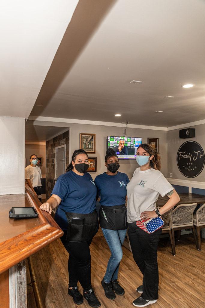 Three staff members smiling under their masks in Freddy J's Bar & Kitchen in Mays Landing, NJ